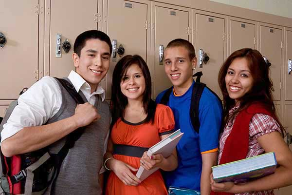 group of young teens standing by lockers